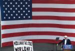 Donald Trump na Florydzie. Plakat głosi, że Hillary Clinton rozpocznie III wojnę światową.