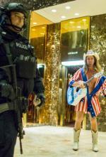 Policjant z niepokojem przygląda się występowi roznegliżowanego kowboja w lobby Trump Tower.