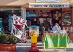 Sardyńskie klimaty. W sklepie wyroby regionalne, przed nim flaga regionu autonomicznego: czerwony krzyż i cztery głowy Maurów (portowa miejscowość Olbia).