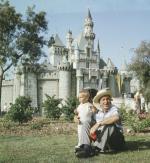 Disney ze swoim wnukiem na terenie Krainy Szczęśliwości, czyli Disneylandu. Pomimo początkowych kłopotów baśniowy park rozrywki od 1955 r. przyciąga tłumy turystów i przynosi krociowe zyski.