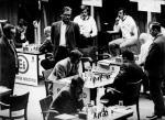 """Bobby Fischer (w centrum) kontra Tigran Petrosjan, Belgrad, 30 marca 1970 roku. Jeden z wielu pojedynków amerykańskiego geniusza z plejadą wspierających się radzieckich szachistów. Tu """"mecz stulecia"""": ZSRR – reszta świata (wygrali Rosjanie, ale tylko 20,5 – 19,5, co było niespodzianką. Partię obserwują wielcy mistrzowie: (stoją od lewej do prawej) Rosjanin Mark Tajmanow, Duńczyk Bent Larsen i Niemiec  z NRD Wolfgang Uhlmann. Fischer (wtedy niespełna 30-letni) był najlepszy w zespole reszty świata, na cztery pojedynki z Petrosjanem dwa wygrał i dwa zremisował"""