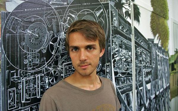 Jan Dziaczkowski przed ścianą ze swym najnowszym fotokolażem