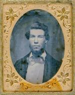 Portret młodego mężczyzny wykonany techniką dagerotypii, umieszczony w ozdobnej metalowej oprawie.