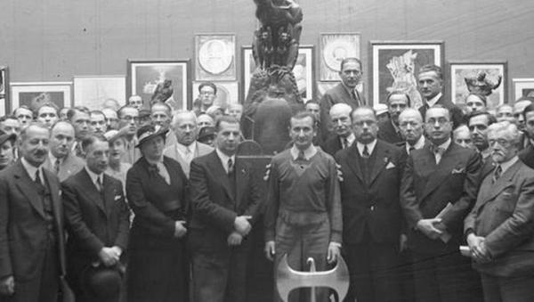 Stanisław Szukalski na wernisażu wystawy w Krakowie w 1936 r. Stoi w środku, przed nim toporzeł jego projektu